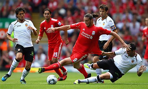 Andy Carroll mixes it with Valencia players at Anfield.